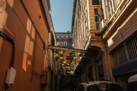 Colorful umbrellas near buildings on city street in Istanbul, Turkey