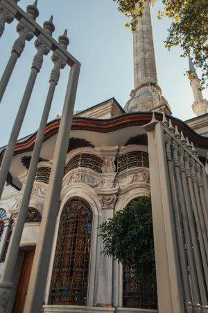 Photo pour Vue en angle bas de l'ornement sur la façade de la mosquée Mihrimah Sultan près de la clôture au premier plan flou, Istanbul, Turquie - image libre de droit