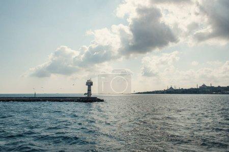Leuchtturm auf Pier im Meer und wolkenverhangener Himmel im Hintergrund in Istanbul, Türkei
