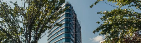 Low angle view of modern building with glass facade in Istanbul, Turkey, banner