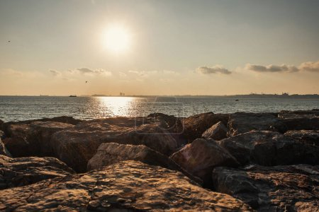 Scenic view of stones on coast of sea during sunset
