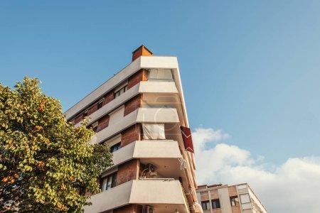 Foto de Vista de ángulo bajo de la casa con balcones y árbol con cielo azul en la calle en Estambul, Turquía - Imagen libre de derechos