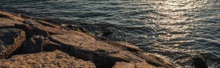 Photo pour Pierres sur la côte de la mer au coucher du soleil, bannière - image libre de droit