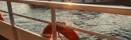 Lifebuoy on railing of ship with sea at background, banner