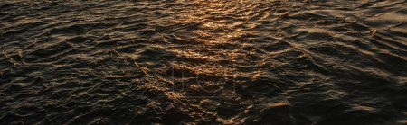 Sunlight on sea water during sunset, banner
