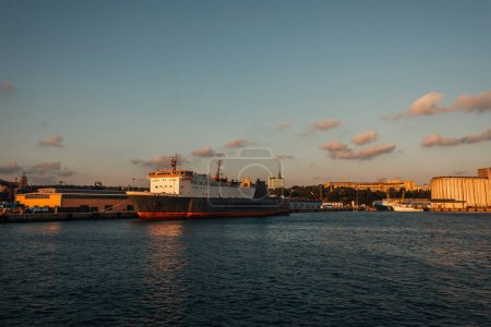 Cargo ship in sea and buildings on coast of Istanbul during sunset, Turkey