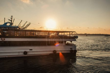 Photo for Boat on water with sun in sky during sunset at background, Istanbul, Turkey - Royalty Free Image