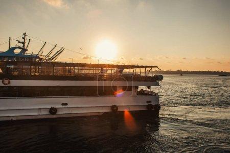 Barco en el agua con sol en el cielo durante la puesta del sol en el fondo, Estambul, Turquía