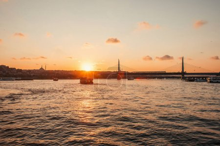 Scenic view of boast in sea, Golden horn metro bridge and sunset sky in Istanbul, Turkey