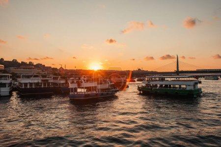 Photo pour Bateaux en mer avec soleil couchant et Golden horn pont de métro à l'arrière-plan, Istanbul, Turquie - image libre de droit