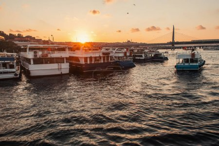 Moored boats near coastline and Golden horn metro bridge with sunset sky at background, Turkey