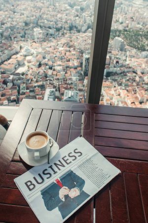 coffee cup and business newspaper on table in cafe with aerial view of Istanbul, Turkey