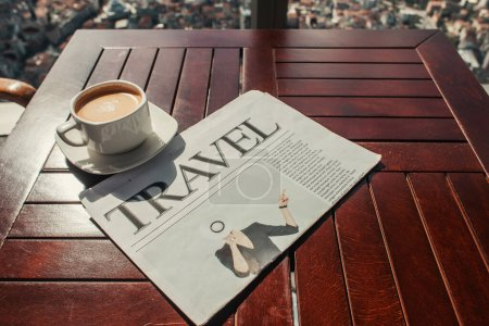 cup of coffee and travel newspaper on wooden table in cafe