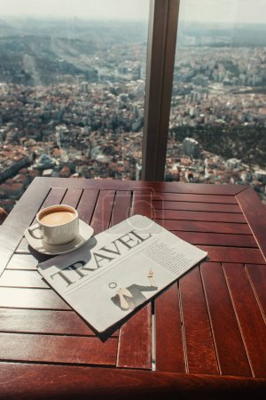 travel newspaper and cup of coffee near window with aerial view of Istanbul, Turkey