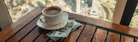 cup of coffee and dollars on wooden table in cafe with aerial view of Istanbul, banner