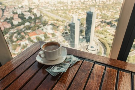 dollars and cup of coffee near cafe window with aerial view of Istanbul