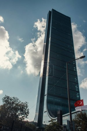Turkish flag, lantern and trees near skyscraper against cloudy sky in Istanbul, Turkey