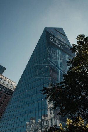 ISTANBUL, TURKEY - NOVEMBER 12, 2020: low angle view of skyscraper with glass facade near green trees