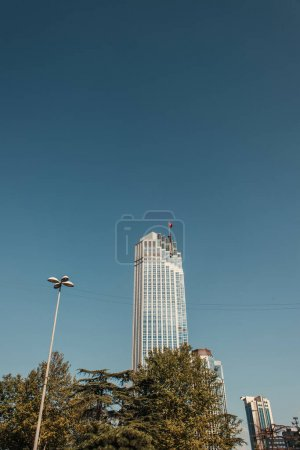 blue, cloudless sky over high, modern building and green trees in Istanbul, Turkey