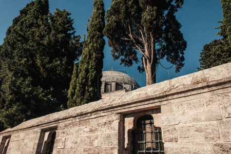 stone wall with fenced windows, and high trees near Mihrimah Sultan Mosque, Istanbul, Turkey