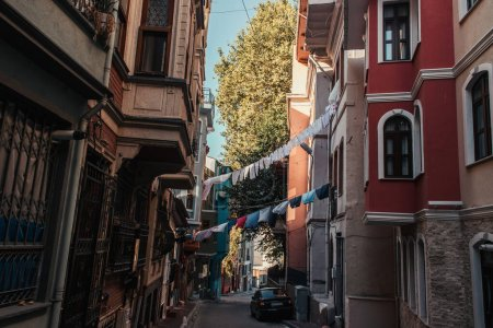 ISTANBUL, TURKEY - NOVEMBER 12, 2020: car and clothesline with laundry between houses on narrow street in Balat