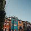 Blue, cloudless sky above colorful houses with gre...