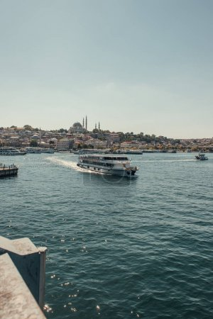 Photo for Touristic ship floating on Bosphorus strait, and view of seafront with moored vessels, Istanbul, Turkey - Royalty Free Image