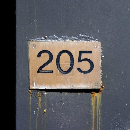 Photo pour Maison numéro deux cent cinq gravée dans une plaque de cuivre - image libre de droit