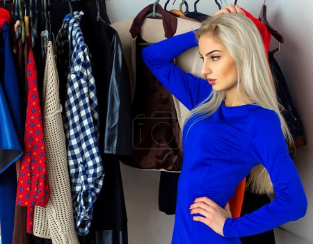 Photo pour Charmante blonde réfléchie choisit des vêtements dans la boutique. Belle jeune fille avec beaucoup de vêtements. Concept commercial . - image libre de droit