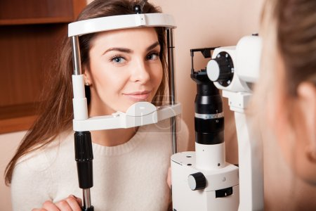 Lovely Young adult woman is having eye exam performed by eye doc