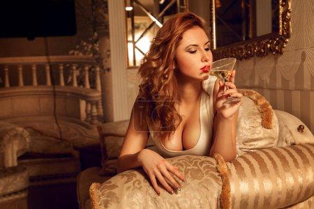 Photo pour Jeune femme chaude avec de gros seins boit du martini. Femme séduisante. Femme sexuelle. le concept de séduction, de plaisir et de désir - image libre de droit