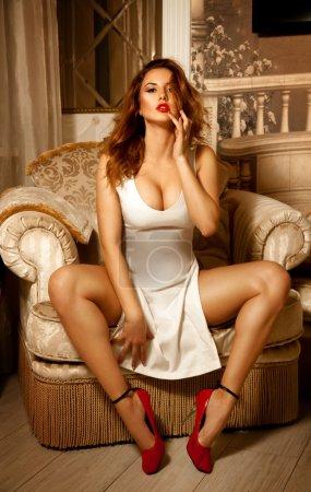 Photo pour Portrait vertical de dame sexuelle en robe blanche posant sur la chaise. Femme séduisante. Femme sexuelle. le concept de séduction, de plaisir et de désir - image libre de droit