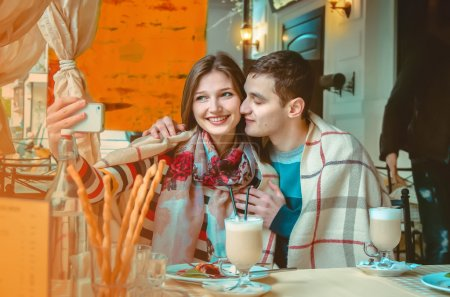Photo for Beautiful couple in love makes selfie on a date in a restaurant - Royalty Free Image