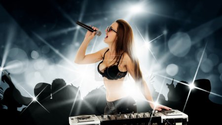Photo for Lovely young Girl DJ is singing to the microphone on a disco party at the night club - Royalty Free Image