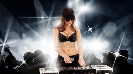 Photo pour Fille DJ dans une casquette avec le mélangeur et microphone dans les lunettes sombres et soutien-gorge noir jouer de la musique sur une fête disco - image libre de droit
