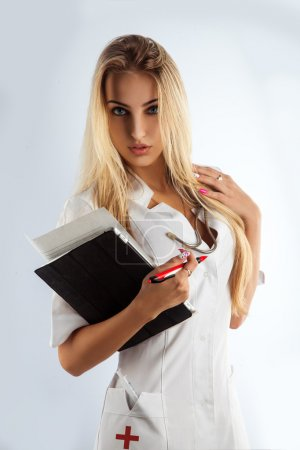 Photo pour Mince infirmière sexy séduire en studio sur fond gris - image libre de droit