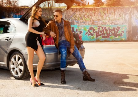 Couple in love flirting sitting at car trunk