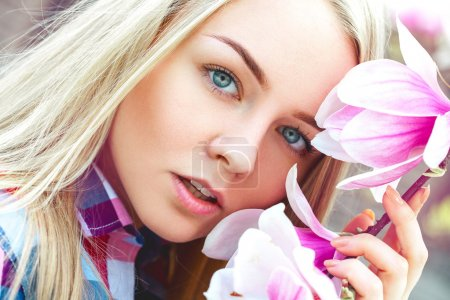 Photo for Outdoors portrait of cutie young blonde woman with pink flowers. Spring time - Royalty Free Image