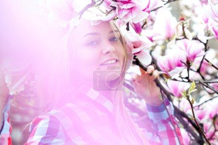 Maravillosa joven rubia sonriendo en flores rosadas