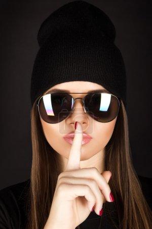 Photo pour Attrayant jeune femme avec une peau saine dans les lunettes de soleil sur fond noir en studio - image libre de droit