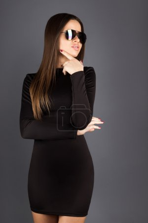 Photo for Adult brunette in black dress and sunglasses looking away in studio on grey background - Royalty Free Image