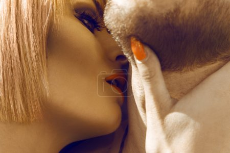 Beautiful blonde woman kissing her boyfriend in neck