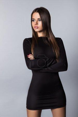 Photo pour Belle jeune brune aux lèvres de silicium regardant loin en studio sur fond gris - image libre de droit