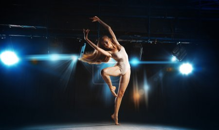 Charming young blonde ballet dancer posing on stage