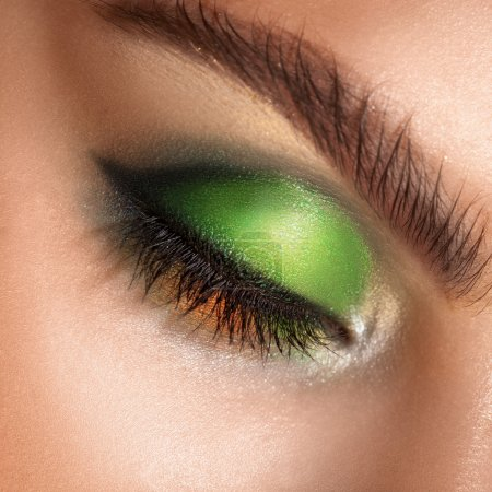 macro photo of closed eyes with professional green colors makeup