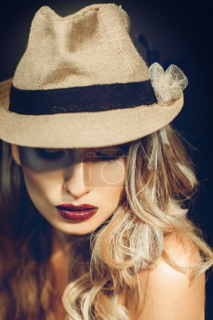 Photo for Sexy adult girl with nice makeup in stylish hat looking down in studio - Royalty Free Image