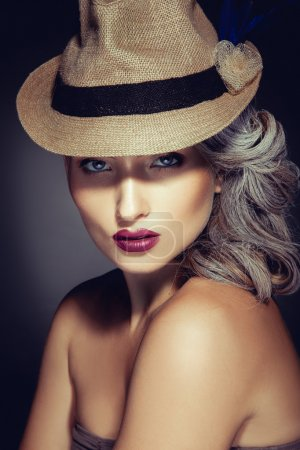 Woman with beautiful makeup and stylish hat looking at camera