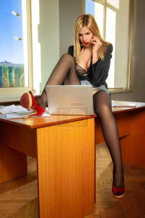 attractive young blonde business woman working in office