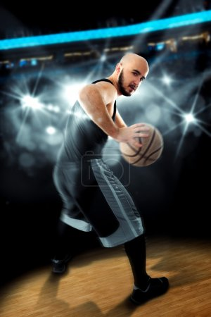 Player in basketball on the floor with ball in hands looking awa