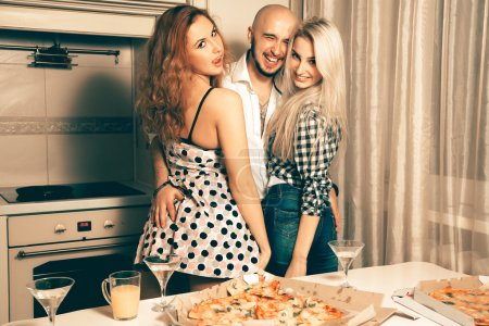 one man with two beautiful girls at home pizza party laughing